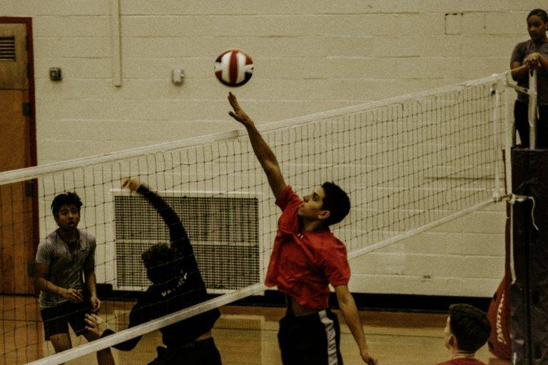 2 boys playing volleyball on court