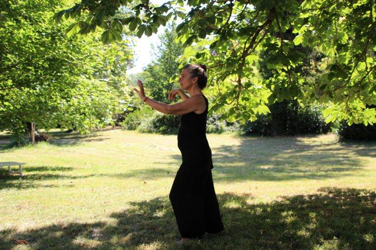woman in black sleeveless dress standing on green grass field during daytime