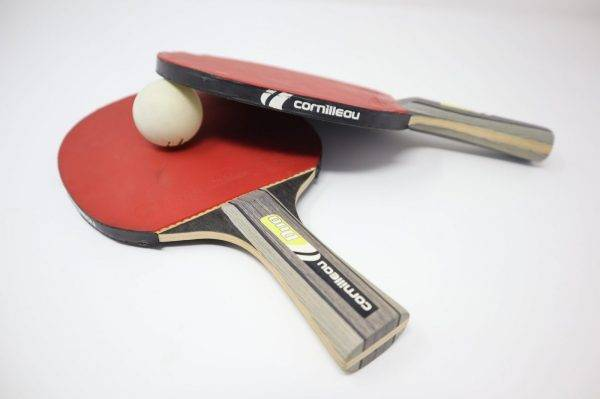 two red pingpong rackets on white surface