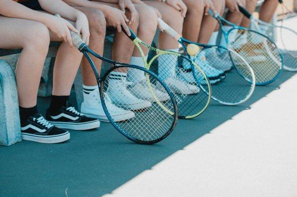 person in black and white nike sneakers holding blue and white tennis racket