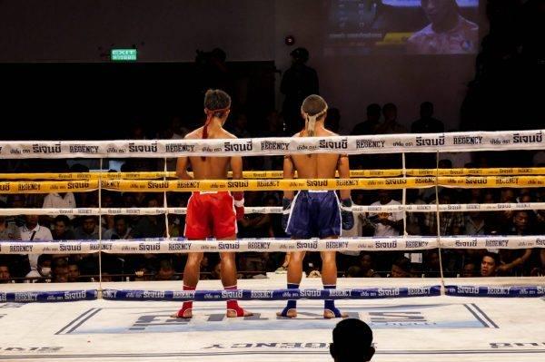 man in blue shorts standing beside man in black shorts